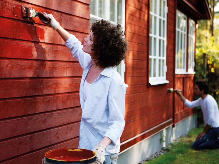 tjej målar huset röd färg